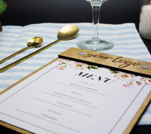wooden menu for restaurant laying on a light blue and white striped mantle